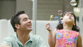 Father with daughter blowing bubbles